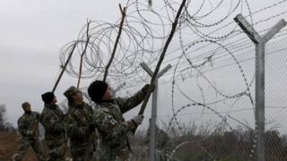 Macedonian Army engineers set a razor wire atop a fence on the border line between Macedonia and Greece