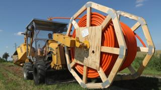 A large work vehicle carrying a mammoth spool of reel rides across open green grassland