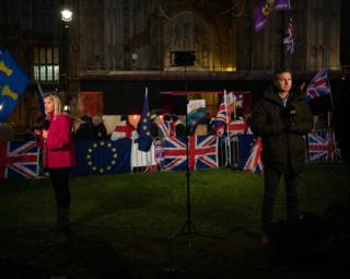 International TV news crews on College Green with flags in the background