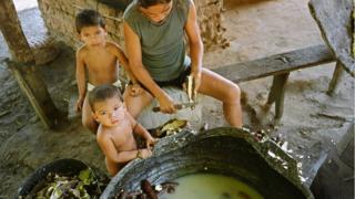Mãe descasca mandioca ao lado de dois filhos na Amazônia
