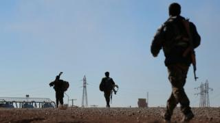 Syria Democratic Forces (SDF) fighters carry their weapons as they walk near the town of Tel al-Saman in the northern rural area of Raqqa, Syria