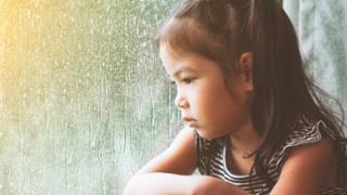 悲傷的女孩盯著下雨的窗外