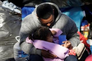 in_pictures A Mexican man embraces his daughter near the Cordova-Americas international border bridge in Ciudad Juarez while waiting to apply for asylum to the US