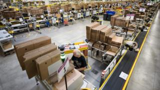 Employees of American electronic commerce company Amazon prepare items for dispatch in Bad Hersfeld, central Germany on December 7, 2017.