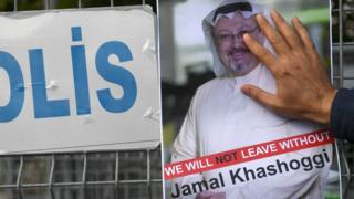 A man puts his hand over a poster of Jamal Khashoggi