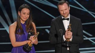 Producer Joanna Natasegara and director Orlando von Einsiedel accept their Oscar award