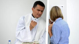 A priest listens to a woman in an open confessional box ahead of a mass in Madrid on September 26, 2014