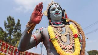 An Indian artist dressed as Lord Rama, a character from a Hindu mythological epic poem entitled Ramayana, gestures during Hanuman Jayanti festival in Bangalore on December 20, 2018.