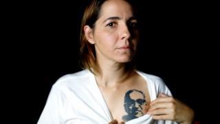 Salvadoran documentalist filmmaker Marcela Zamora shows her tattoo of the late Archbishop of San Salvador