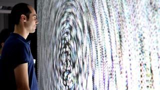 Мужчина рассматривает экран с пузырьками, которые помогают найти баланс при повреждении внутреннего уха. Университет Гренобля, Франция, ноябрь 2017 года.