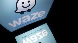 The logo of mobile app 'Waze' is displayed on a tablet