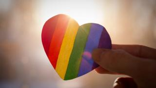 Rainbow coloured paper heart held in hand