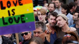 """Two men embrace behind a sign saying """"love is love"""" at a rally for marriage equality in Australia"""
