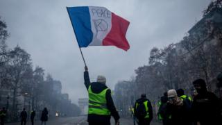 "A protester waves a flag during the ""yellow vests"" demonstration in Paris France"