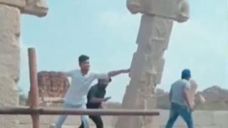 Screengrab from a viral video showing three men shoving a pillar in Hampi