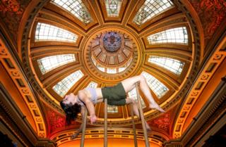 Acrobat Alyssa Moore is held up by poles with an ornate ceiling in the background