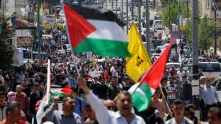 Palestinians take part in a protest in solidarity with Palestinian prisoners held by Israel