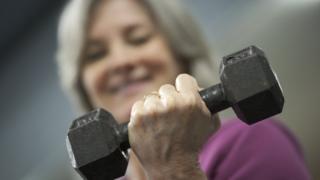 A woman raises weight