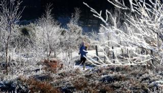 A woman running through frozen countryside