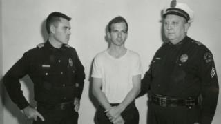 Oswald y dos agentes de policía.