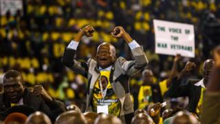 """Zimbabwe War veterans sing and dance ahead of a consultative meeting between the veterans of Zimbabwe""""s liberation war and leaders of Zimbabwe ruling party Zimbabwe African National Union Patriotic Front (ZANU PF) in Harare on May 11, 2018."""