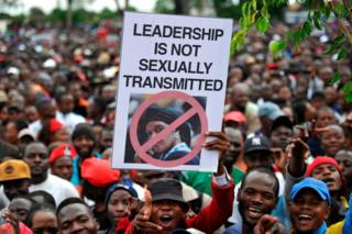 Anti-Mugabe protesters in Zimbabwe mass in Harare, one of whom holds a signs which reads 'leadership is not sexually transmitted'.