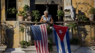 In this Dec. 19, 2014 file photo, Javier Yanez stands on his balcony decorated with US and Cuban flags in Old Havana, Cuba.