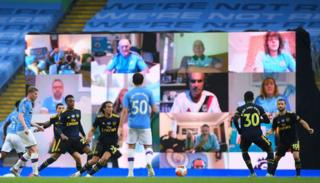 Manchester City fans shown on a giant screen at the Etihad Stadium