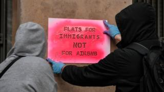 """Activists stencil a slogan reading """"Flats for immigrants not for airbnb"""" on a wall during a demonstration in Athens."""