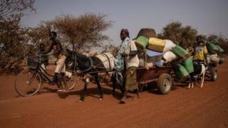 People with their belongings piled on a makeshift trailer pulled by a donkey
