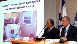 An image of 13-year-old Palestinian Ahmad Manasra is screened during a press conference attended by Israeli Prime Minister Benjamin Netanyahu (R) on 15 October 2015, at the foreign ministry in Jerusalem.