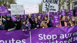 Women carry purple protest signs