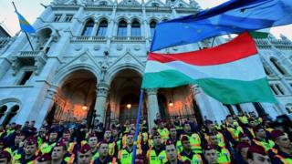 People protest in front of lines of police officers at the parliament building at Budapest