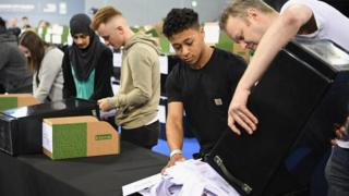 volunteers tipping ballot papers out of box at local election count