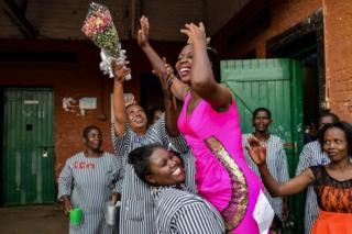 Inmates at Kodiaga Womens Prison celebrate with the newly selected Miss Kodiaga Womens Prison 2019, who is wearing a bright pink dress with glitter on one side, as well as a tiara, in Kisumu, Kenya - Saturday 17 February 2019
