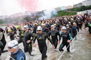 Swimmers race to the sea on Tenby's North Beach