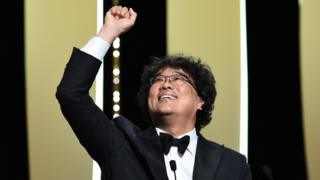 "Director Bong Joon-Ho (L) reacts after winning the Palme d""Or award for ""Parasite"" on stage during the Closing Ceremony of the 72nd annual Cannes Film Festival on May 25, 2019 in Cannes, France."
