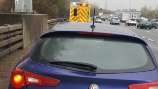 A car and an ambulance parked on the hard shoulder of the M25