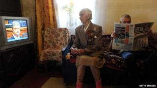 Elderly woman watches TV while man reads a newspaper