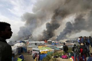 """Migrants look at burning makeshift shelters and tents in the """"Jungle"""" on the third day of their evacuation and transfer to reception centres in France, as part of the dismantlement of the camp in Calais, France, 26 October 2016."""