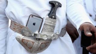 مواطن عربي يحمل هاتفا محمولا