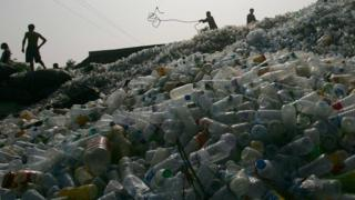 Workers on a pile of plastic bottles in China