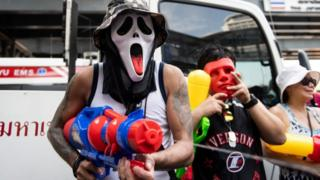 A reveller uses a water gun as people celebrate the Buddhist New Year, locally known as Songkran, in Bangkok on 13 April 2019.