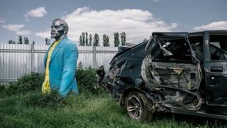 Una estatua de Lenin en un depósito de autos viejos