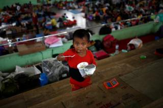 A child eats noodles at a temporary evacuation center for people living near Mount Agung, a volcano on the highest alert level, inside a sports arena in Klungkung, on the resort island of Bali, Indonesia, 24 September 2017.
