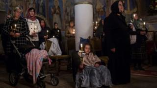 A young girl closes her eyes as she and other Serbian Orthodox Christians hold candles during a midnight Easter service at a monastery in the village of Sukovo