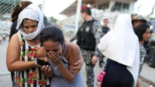 Relatives of inmates react in front of a prison complex in the Brazilian state of Amazonas