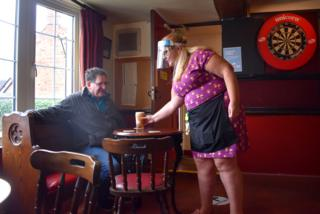 A woman serves a pint to customer in a pub