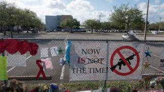 "A sign at floral tribute at Parkland school reads ""Now is the time"" with a symbol of a gun crossed out"