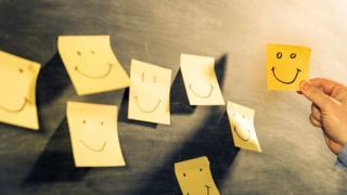Pequenos pedaço de papel com carinhas felizes